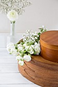 White ranunculus and gypsophila on brown chip-wood boxes
