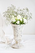 White ranunculus and gypsophila in stone vase