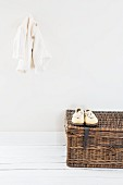 Cardigan hung on wall above white shoes on wicker trunk