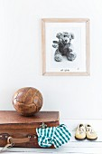 Picture on wall above teddy bear, old ball, leather suitcase and children's shoes