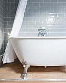 Free-standing bathtub with claw feet against grey wall tiles