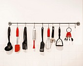 Black and red kitchen utensils hung from hooks on bar