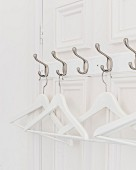 White coathangers hung from row of hooks on panelled door