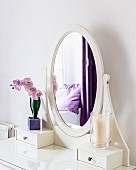 Oval mirror on dressing table in room with purple accents