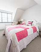 Pink and white quilt on bed below gable ceiling