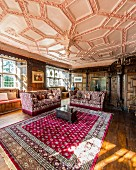 Wood-panelled walls and ornate stucco ceiling in grand living room