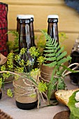 Bottles of beer wrapped in paper and decorated with dill flowers and ferns on dresser