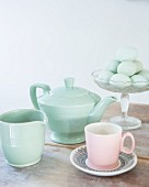 Retro teapot, milk jug and pink teacup in front of eggs in glass bowl
