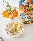 Posy in beaker, muffin with bite missing on child's plate in front of stacked of children's books