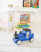 Blue toy train on white wooden floor in child's bedroom