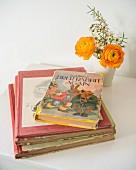 Retro children's books next to posy in beaker on white children's table