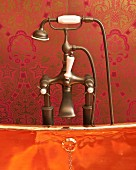 Edge of shiny copper bathtub and vintage tap fittings against red brocade wallpaper