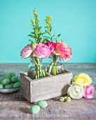 Ranunculus in glass bottles in wooden box and Easter decorations