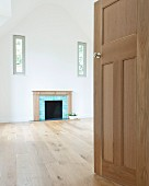 View into empty, high-ceilinged room with open fireplace between windows in gable-end wall