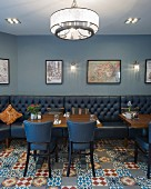 Leather benches and chairs on ornamental floor tiles in retro restaurant in shades of blue