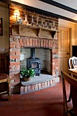 Log-burning stove in traditional brick fireplace below glass carafes on rustic bracket shelf