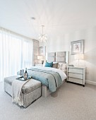 Champagne cooler on tray on ottoman at foot of bed in elegant bedroom