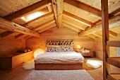 Schlafzimmer unter dem Dach in einem Holzhaus