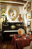Antique gilt-framed painting above piano and table