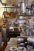 Antique cooker, copper pans and open-fronted shelves in kitchen