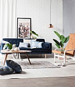 Cushions with denim cover on the blue couch and on the floor, coffee table, leather-covered chair, houseplant and pendant lamp in the living room with retro flair