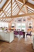 Large dining table below open roof structure in kitchen-dining room