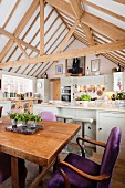 Dining table in country-house kitchen-dining room below open roof structure
