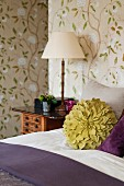 Green flower-shaped scatter cushion on bed against floral wallpaper