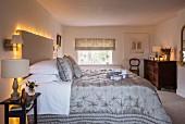 Lichterkette dekoriertes Betthaupt im ländlichen Schlafzimmer