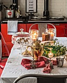 Festive arrangement of gold coffee pot and lit candles in front of red range cooker in kitchen