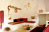 Whitewashed lounge with red accents in renovated trullo