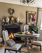 Upholstered chairs around pedestal table in front of open fireplace