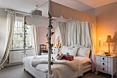 Four-poster bed in white candlelit bedroom