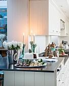 Weihnachtlich dekorierte Küchentheke mit Kuchen und Blumen