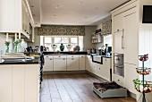 Große moderne Landhausküche in Weiß mit schwarzer Arbeitsplatte