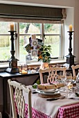 Table set for Christmas dinner in front of antique candlesticks and Christmas cards on console table