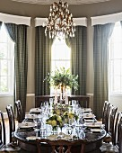 Table festively set with white roses below glass chandelier