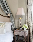 Elegant bedside table with lamp and family photograph