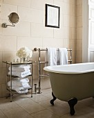 Free-standing bath and towel rails in bathroom with tiled walls and floor
