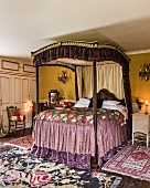 Antique four-poster bed with flounces in colourful bedroom