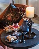 Brennende Kerze auf einem Beistelltisch mit Gebäck