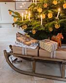 Verpackte Geschenke auf einem Schlitten unter dem Weihnachtsbaum