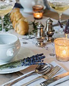 Table festively set with lavender and tealight holders