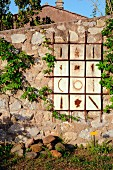 Artwork on stone wall in Mediterranean garen