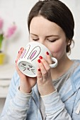 Young woman drinking from white DIY Easter mug with hand-drawn bunny motif