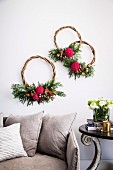 Three wreaths of curved branches with flowers above the sofa