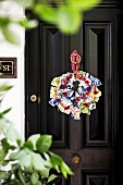 Wreath of brightly patterned fabrics on a black front door