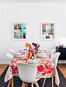 Bunt gedeckter Tisch mit Blumensträußen vor bunten Bildern