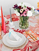 Colorfully laid table with bouquet and colored candles