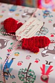 Small red knitted mittens used as gift tags